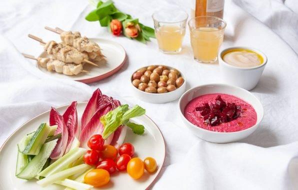 Gezonde bietendip, witte bonendip, olijven en kipspiesjes op een picknickkleed