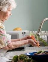 Oma kookt een gezonde stamppot van aardappelen en wortel