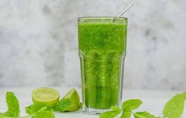 Groene komkommer smoothie met appel en limoen met blaadjes munt