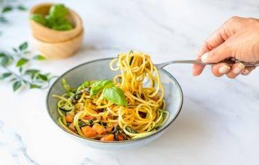 courgette pasta tomaat paprika parmezaan op een bord