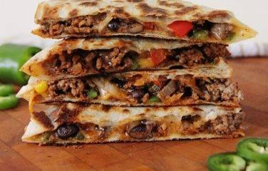 stapeltje quesadillas met gekruid gehakt en gesmolten kaas op het aanrechtblad