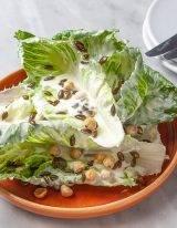 Romaine Sla bladeren met geitenkaas dressing en geroosterde pompoenpitten en hazelnoten
